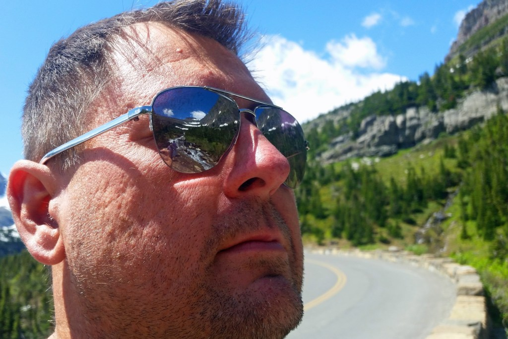 Reflection in glasses staring at a waterfall Glacier National Park