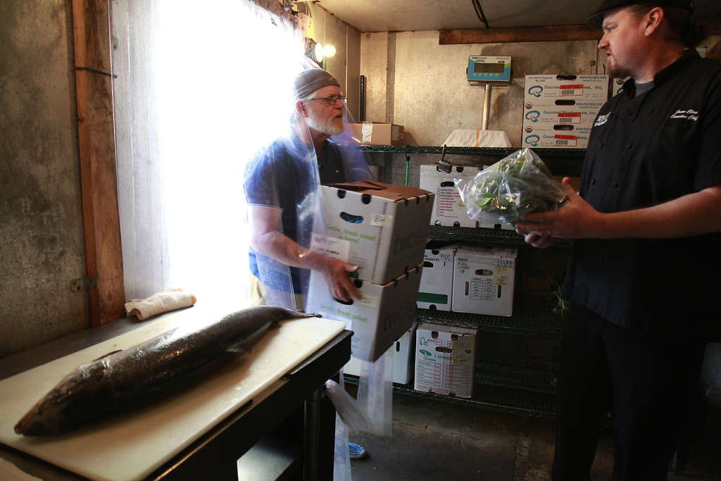 Men carrying boxes of produce in a refrigerated room