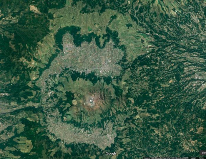 Sur cette photo satellite, on devine bien le volcan au centre avec différents monts, la caldeira en forme de fer à cheval et les falaises qui la bordent en vert foncé