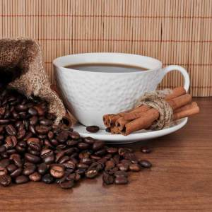 a bundle of cinnamon stick sits in the saucer of a filled, white coffee cup; roasted coffee beans are spilled on the table beside the cup.