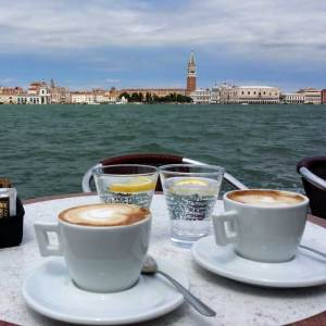 On a seaside table sit cups of coffee with heavy crema.
