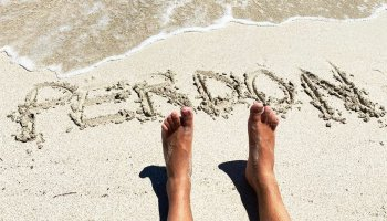 Perdón escrito en la arena de la playa