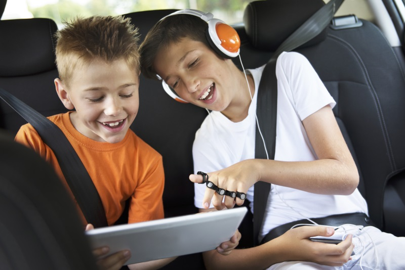 Two children using Tap to play games on a long car ride with their iPad