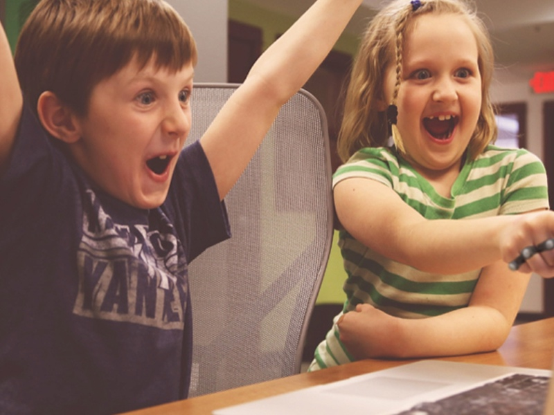 Two excited children using Tap to play their favorite game on their mac computer