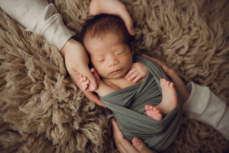 newborn in parents hands holding dad's thumb Oshawa
