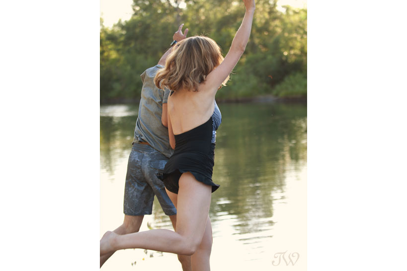 couple jumps into a swimming hole captured by Tara Whittaker Photography