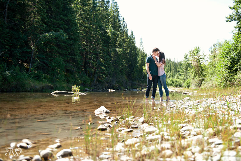 couple wade in a river during engagement pictures by Tara Whittaker Photography