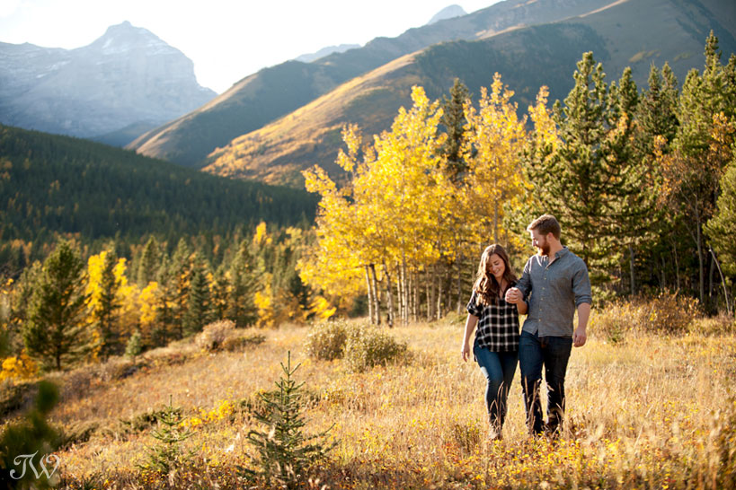 couple walk in the Rocky Mountains during their fall engagement session captured by Tara Whittaker Photography