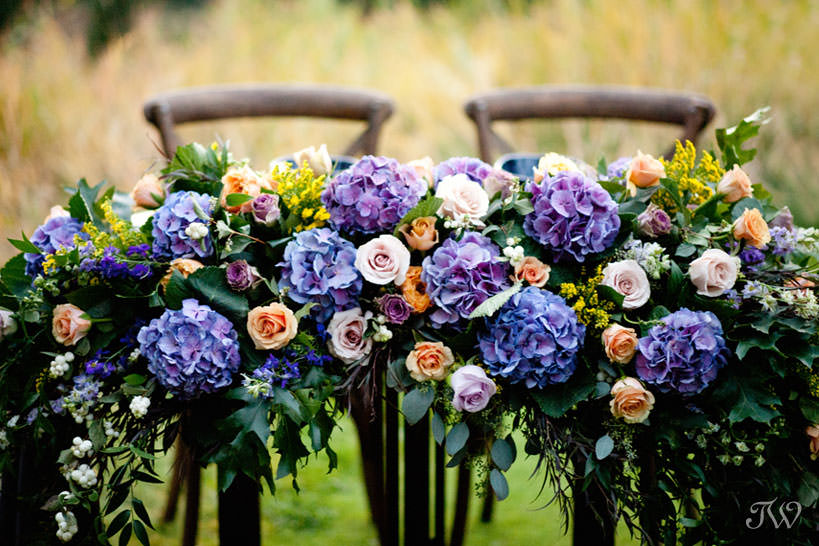 flowers adorn a sweet table at a Silvertip wedding captured by Calgary wedding photographer Tara Whittaker
