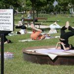 Mnóstwo ludzi ćwiczy jogę w parku