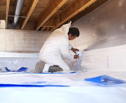 installing crawl space insulation and vapor barrier