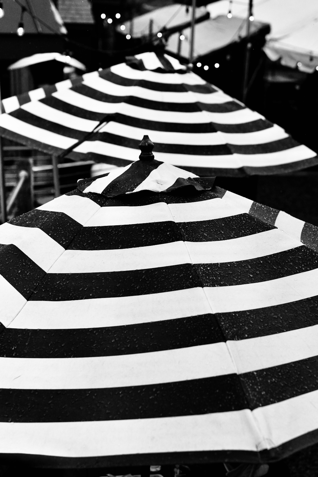 The tops of two black and white striped umbrellas in the rain. 2021. Taryn Okesson. Digital Photography. Littleton, New Hampshire.