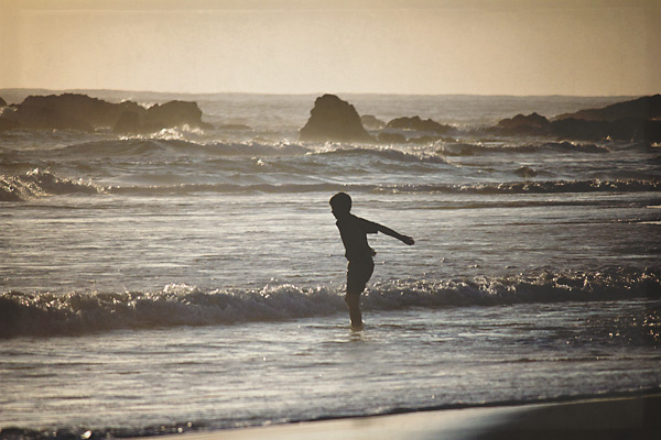 Boy in the surf at sunrise