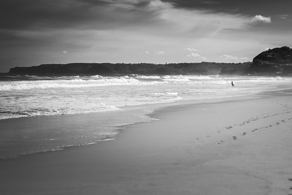 black and white beach and surfer photograph