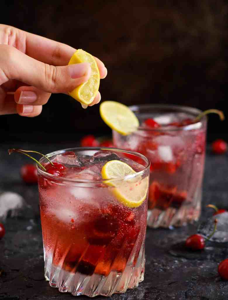 Cherry Gin And Tonic refreshing summer cocktail with a squeeze of lemon juice