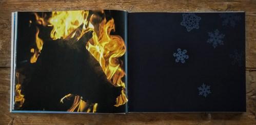 pimeä aukeama jännittävästä hahmosta tulen loimussa ja graafisista lumihiutaleista