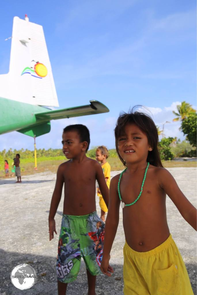 Children playing around the plane at Maiana airport.