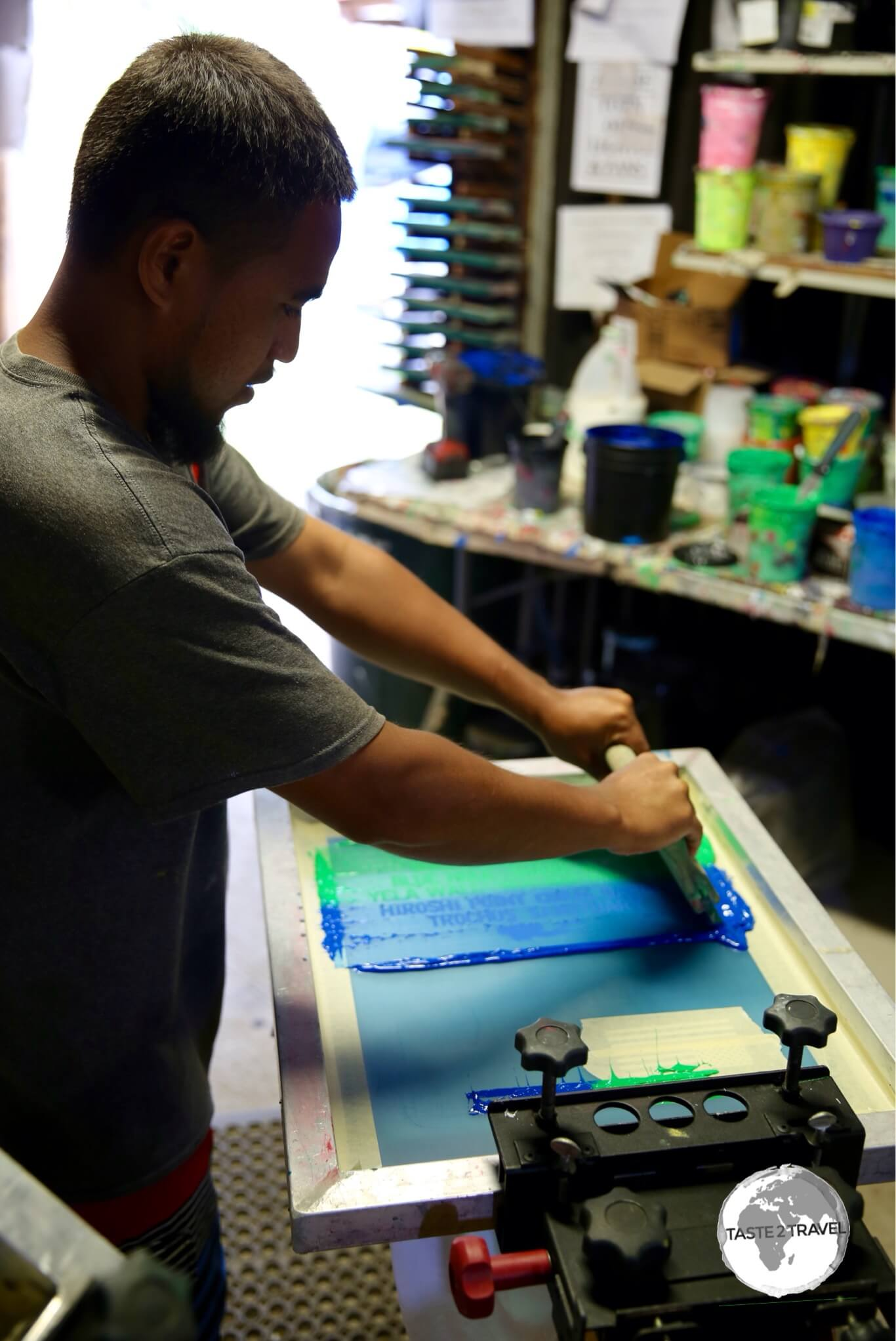 Screen printing the design onto the t-shirts.