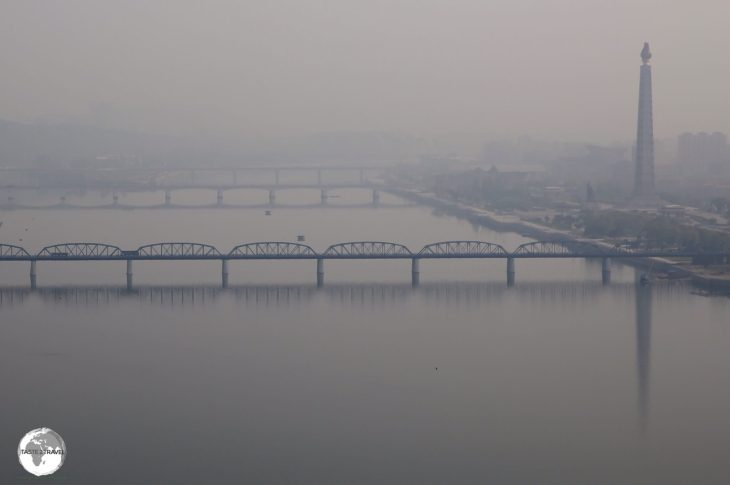 An early morning view, from my hotel room, of the Taedong River in Pyongyang, with the <i>Juche Tower</i> standing sentinel on the right bank.