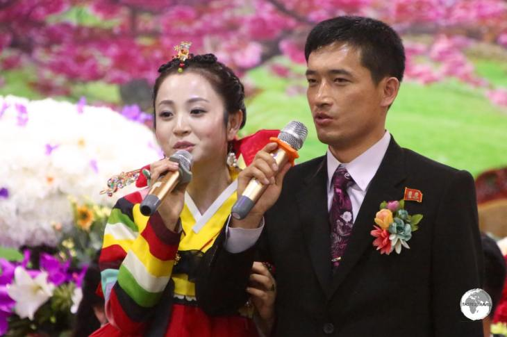 Newlyweds performing Karaoke at their wedding reception which was held in a private room at a bar in Pyongyang.