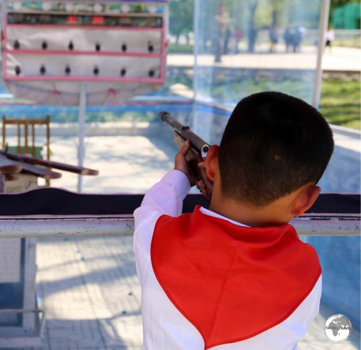 A young school boy tries his luck at the shooting alley at Mt Taesong Amusement park.