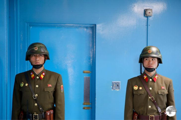 The blue door is the exit to South Korea. The guards ensure no one leaves the room through this door.