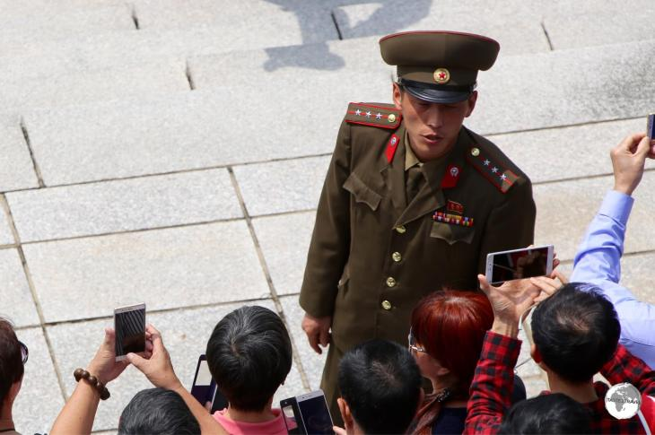 A North Korean soldier conducting a tour of the DMZ with a group of Chinese tourists.