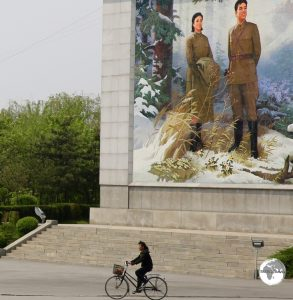 A cyclist in Nampo passes in front of a giant propaganda image featuring a young Kim Il-sung and his wife.
