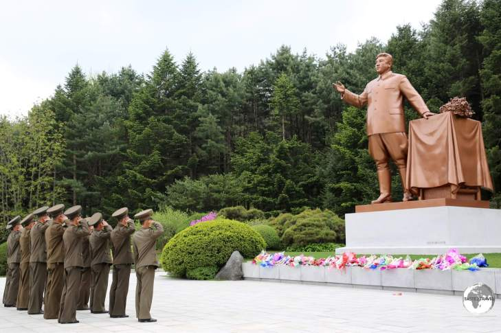 Soldiers salute in front of a statue of Kim il-sung.