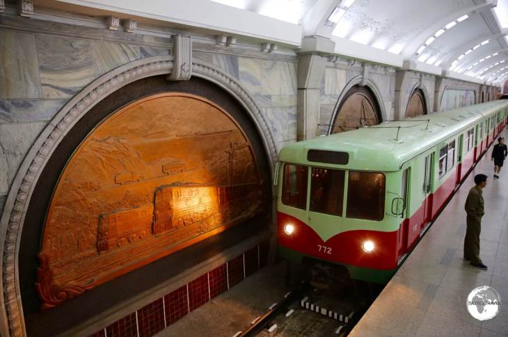The headlight from a locomotive illuminates one of the bronze panels at Puhung station on the Pyongyang metro.