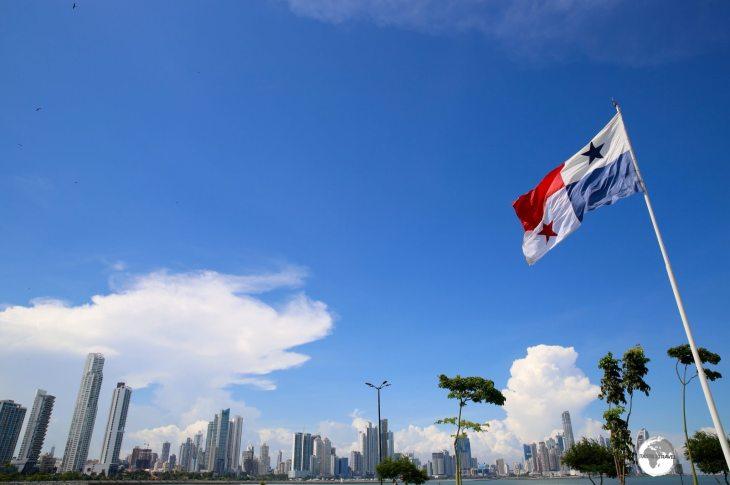 The Panama flag and the modern skyline of Panama City, a thriving metropolis.