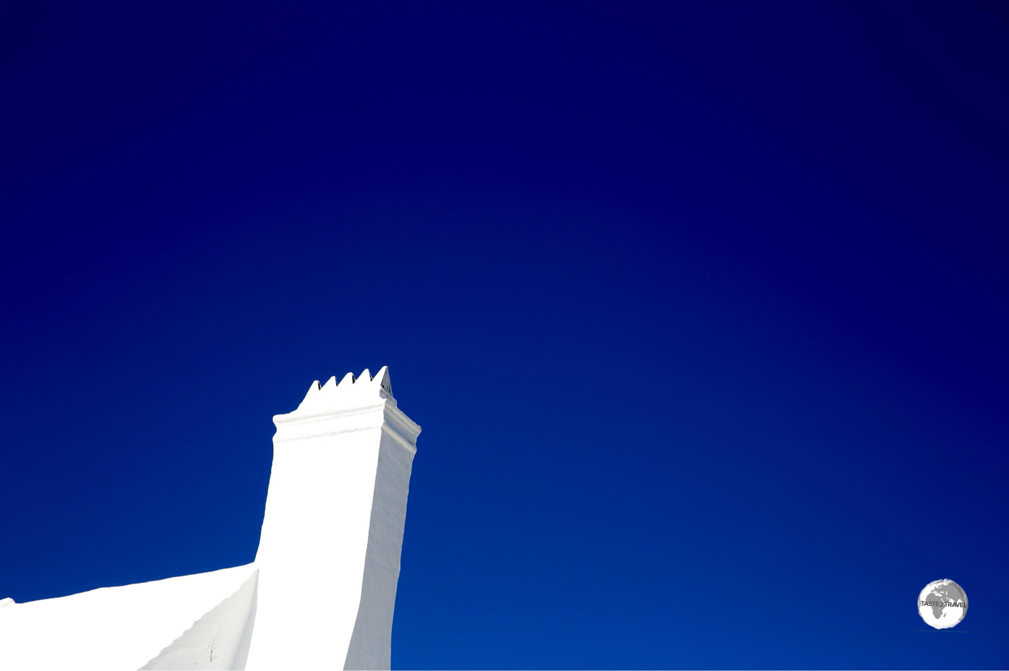 White chimney against a brilliant blue sky.