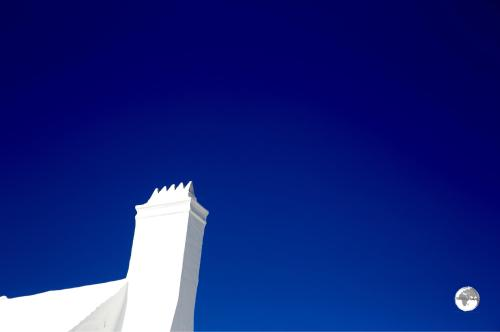 A white chimney in St. Georges contrasts starkly against a cloudless blue sky.