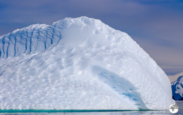 An iceberg glowing in the morning sun in the Graham passage. The dimpled effect is caused by water action when the iceberg is below the waterline.