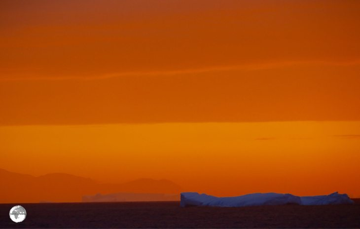 An iceberg illuminated against the sky of a setting sun.