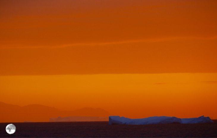 An iceberg illuminated against the sky of a setting sun.