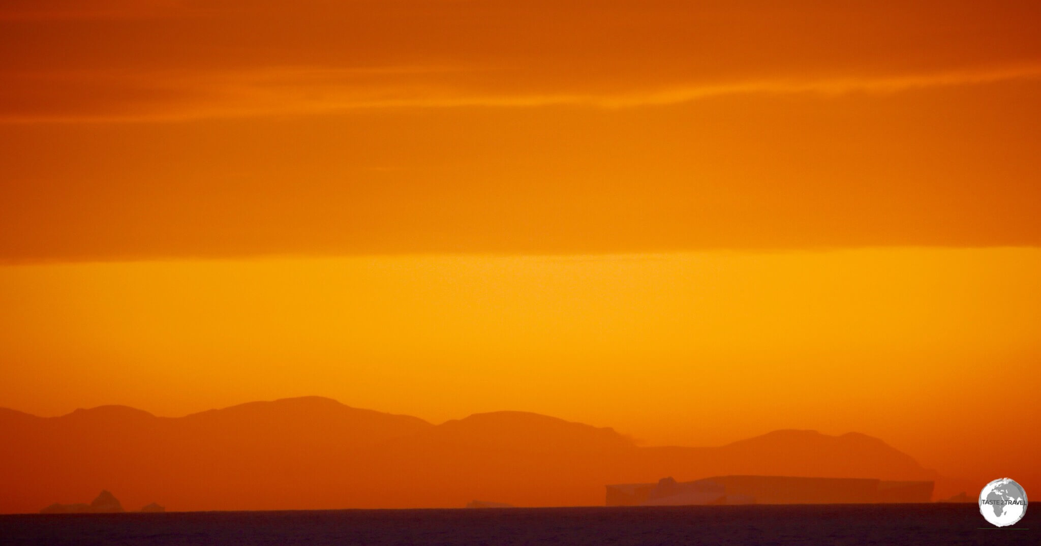The rectangular shape of an iceberg stands out against a mountain range in the setting sun.