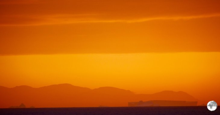 The darkened, rectangular form of a large iceberg stands out against a mountain range in the setting sun.