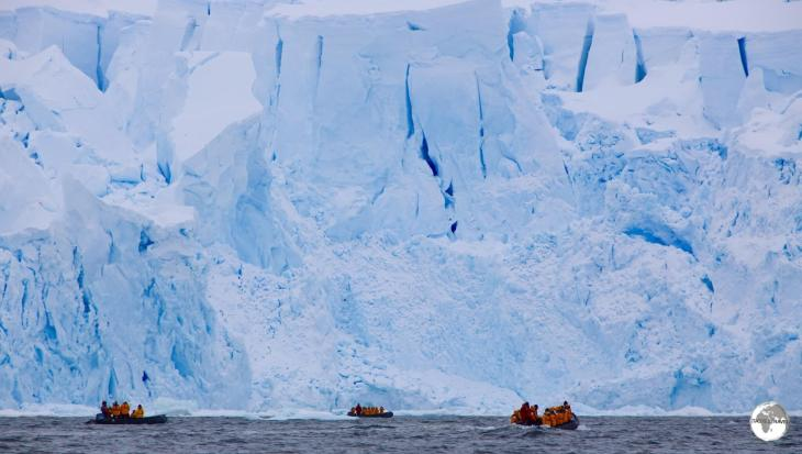 The impressive, soaring ice wall of the glacier in Andvord Bay dwarfs our Zodiacs.