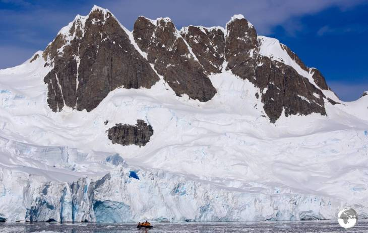 A Zodiac in the Graham passage is dwarfed by the towering peaks of Graham Land.