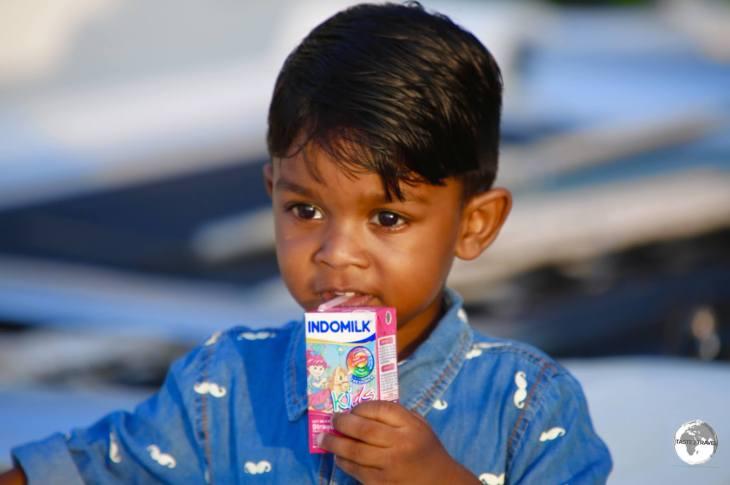 A young boy, enjoying his milk, on Maafushi Island.