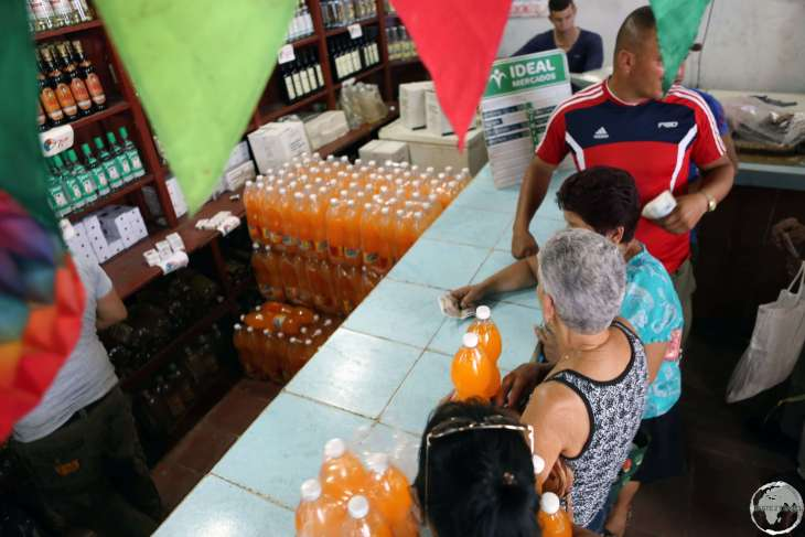 Lining up to buy orange soda which had just arrived by the pallet load at a shop in Cigar maker working in a factory in downtown Sancti Spíritus.
