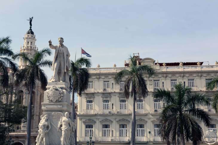 A statue of José Martí in Central Park with the <i>Hotel Inglaterra</i> in the background.