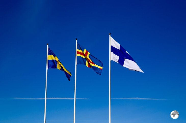 The flag of the Åland Islands (centre) surrounded by the flags of its all important, powerful neighbours - Sweden and Finland.
