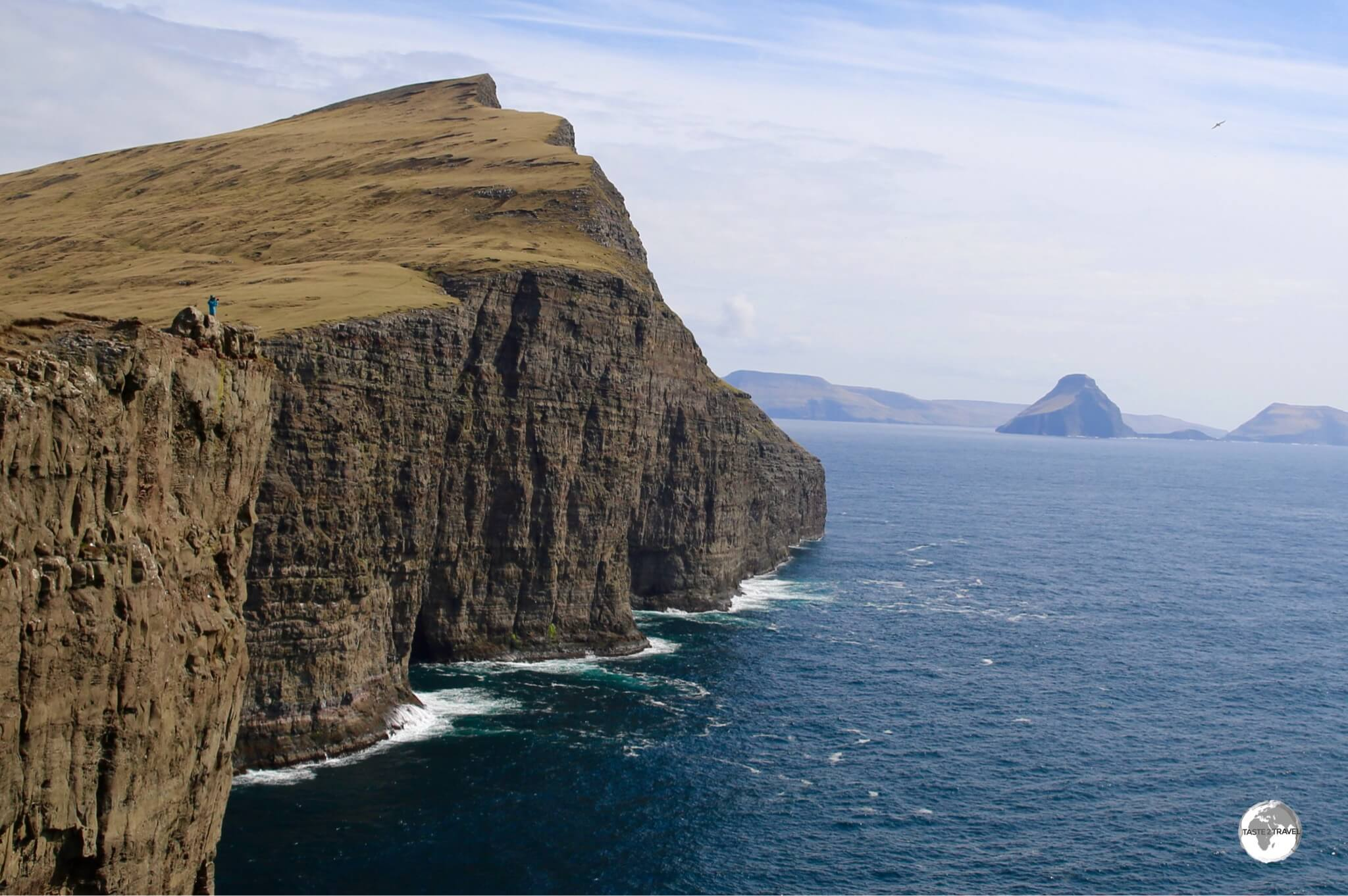 A lone hiker provides a sense of scale to the soaring cliffs on Vagur island.