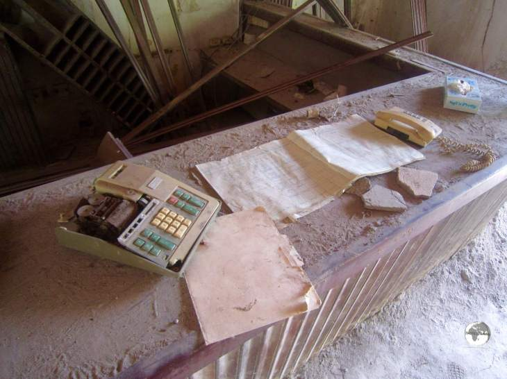 A calculator and ledger book remain on the reception desk of the abandoned Montserrat Springs Hotel,