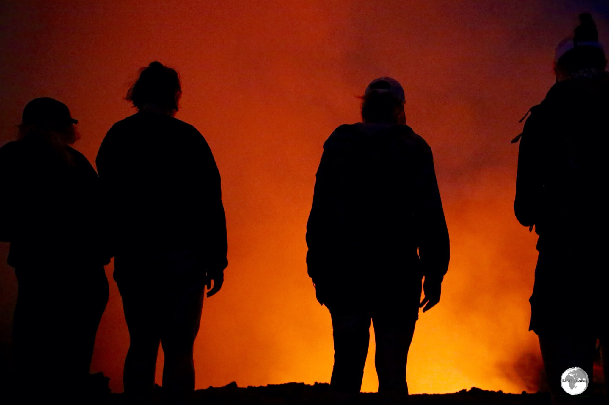 Observers illuminated by the glow from the volcano.