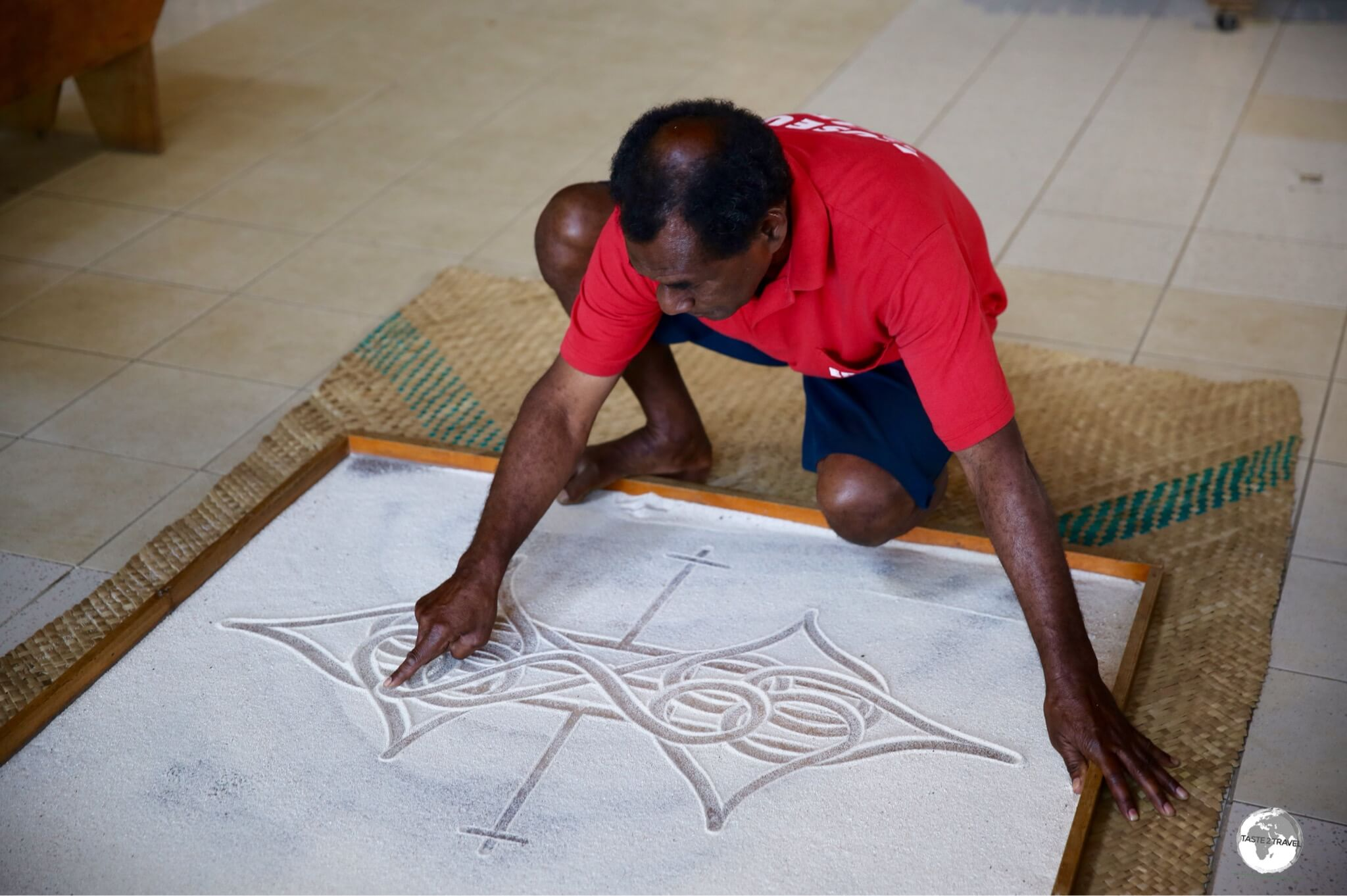 Edgar Hinge of the National Museum, telling a story using the ancient art of Sand-drawing.