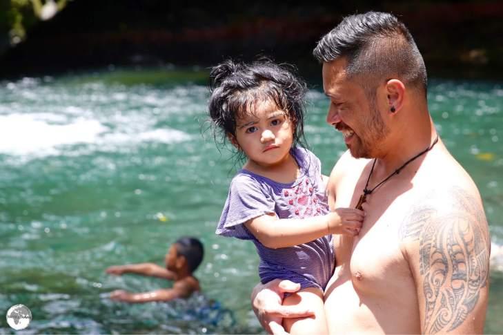 A Samoan family enjoying a swim at the Togitogiga Waterfalls.