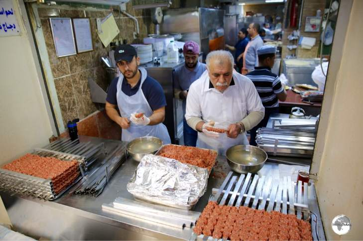 Two chefs preparing many Kofte shish kebabs at Souk Al-Mubarakiya.